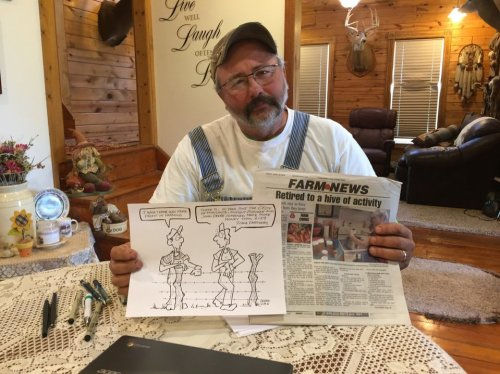 Rick Friday holding the cartoon that got him fired from Farm News as well as a copy of the newspaper.